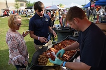 """Dustin Polovich, """"First Sergeants Council"""" team member, serves crawfish and 'fixins' to Medea Cook, 81st Medical Support Squadron system administrator, and her son, Mathew, during the 6th Annual Bay Breeze Crawfish Cook-Off at the Bay Breeze Event Center at Keesler Air Force Base, Mississippi, April 7, 2017. The """"Craw-Fish Pot-Nahs"""" won first place overall and a free entry into the 26th Annual Mississippi Coast Coliseum Crawfish Festival Cook-Off. (U.S. Air Force photo by Kemberly Groue)"""