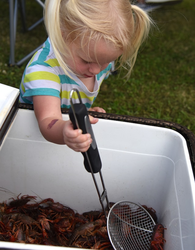 """Ariana Crane, daughter of U.S. Air Force Maj. Brooks Crane, 81st Medical Group group practice manager, catches live crawfish during the 6th Annual Bay Breeze Crawfish Cook-Off at the Bay Breeze Event Center at Keesler Air Force Base, Mississippi, April 13, 2018. The """"Craw-Fish Pot-Nahs"""" won first place overall and a free entry into the 26th Annual Mississippi Coast Coliseum Crawfish Festival Cook-Off. (U.S. Air Force photo by Kemberly Groue)"""