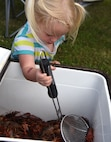 """Ariana Crane, daughter of U.S. Air Force Maj. Brooks Crane, 81st Medical Group group practice manager, catches live crawfish during the 6th Annual Bay Breeze Crawfish Cook-Off at the Bay Breeze Event Center at Keesler Air Force Base, Mississippi, April 7, 2017. The """"Craw-Fish Pot-Nahs"""" won first place overall and a free entry into the 26th Annual Mississippi Coast Coliseum Crawfish Festival Cook-Off. (U.S. Air Force photo by Kemberly Groue)"""