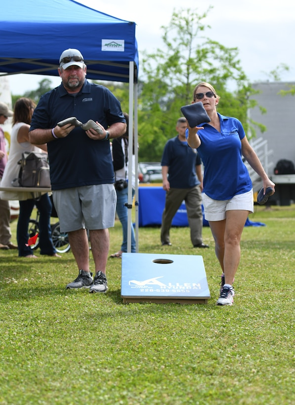 "Michael Fix, 81st Force Support Squadron deputy director, and U.S. Air Force Lt. Col. Teresa Ammons, 81st FSS commander, play corn hole during the 6th Annual Bay Breeze Crawfish Cook-Off at the Bay Breeze Event Center at Keesler Air Force Base, Mississippi, April 13, 2018. The ""Craw-Fish Pot-Nahs"" won first place overall and a free entry into the 26th Annual Mississippi Coast Coliseum Crawfish Festival Cook-Off. Twenty-one teams competed in the event with over 800 Keesler personnel in attendance and almost 1700 pounds of crawfish distributed. (U.S. Air Force photo by Kemberly Groue)"