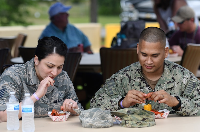 "U.S. Air Force Tech. Sgt. Cassandra Cruz, 81st Force Support Squadron Airmen Leadership School instructor, and U.S. Navy Chief Gunners Mate Kiko Cruz, Navy Recruiting Command naval officer recruiter, District New Orleans, Louisiana, eat crawfish during the 6th Annual Bay Breeze Crawfish Cook-Off at the Bay Breeze Event Center at Keesler Air Force Base, Mississippi, April 13, 2018. The ""Craw-Fish Pot-Nahs"" won first place overall and a free entry into the 26th Annual Mississippi Coast Coliseum Crawfish Festival Cook-Off. (U.S. Air Force photo by Kemberly Groue)"