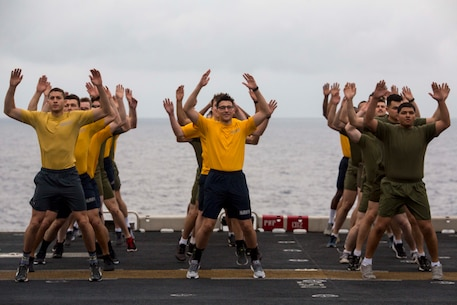 Marines and Sailors do jumping jacks on the flight deck of the USS Wasp (LHD-1) during Sgt. Maj. PT while underway in the Philippine Sea, April 11, 2018.