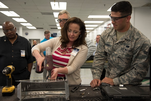 Dana Lancellotti, an Air Mobility Command civic leader, uses a drill during a fabrication flight demonstration at MacDill Air Force Base, Florida, April 12, 2018. The fabrication flight demo was part of a three-day tour where more than 30 civic leaders throughout various AMC communities gathered to gain insight about how MacDill fits into AMC's overall mission and global reach capabilities. (U.S. Air Force photo by Airman 1st Class Ashley Perdue)