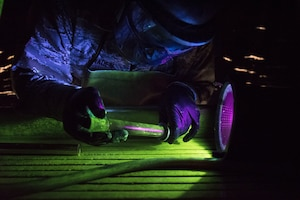 An Airman looks at an aircraft part beside a black light.