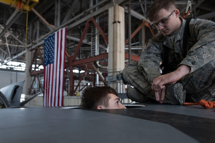 An Airmen looks down at another Airmen who is in the wing of an aircraft.