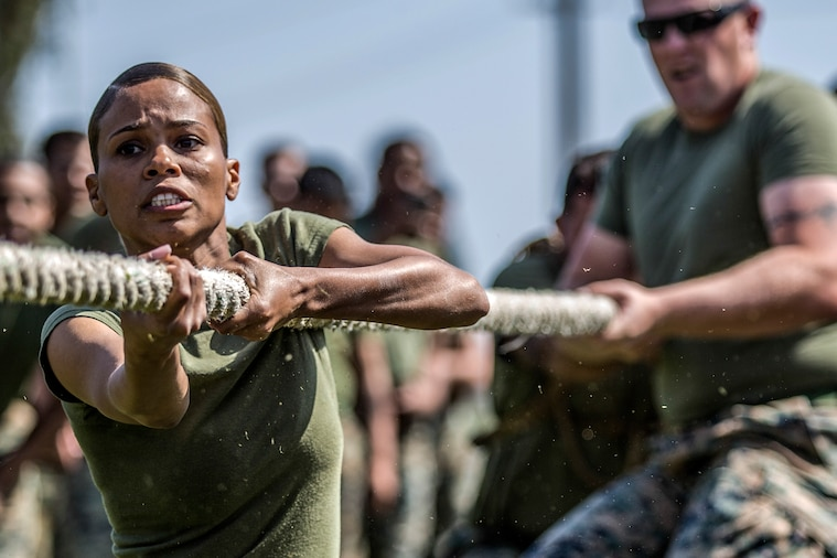Two Marines pull on a rope during tug-of-war.