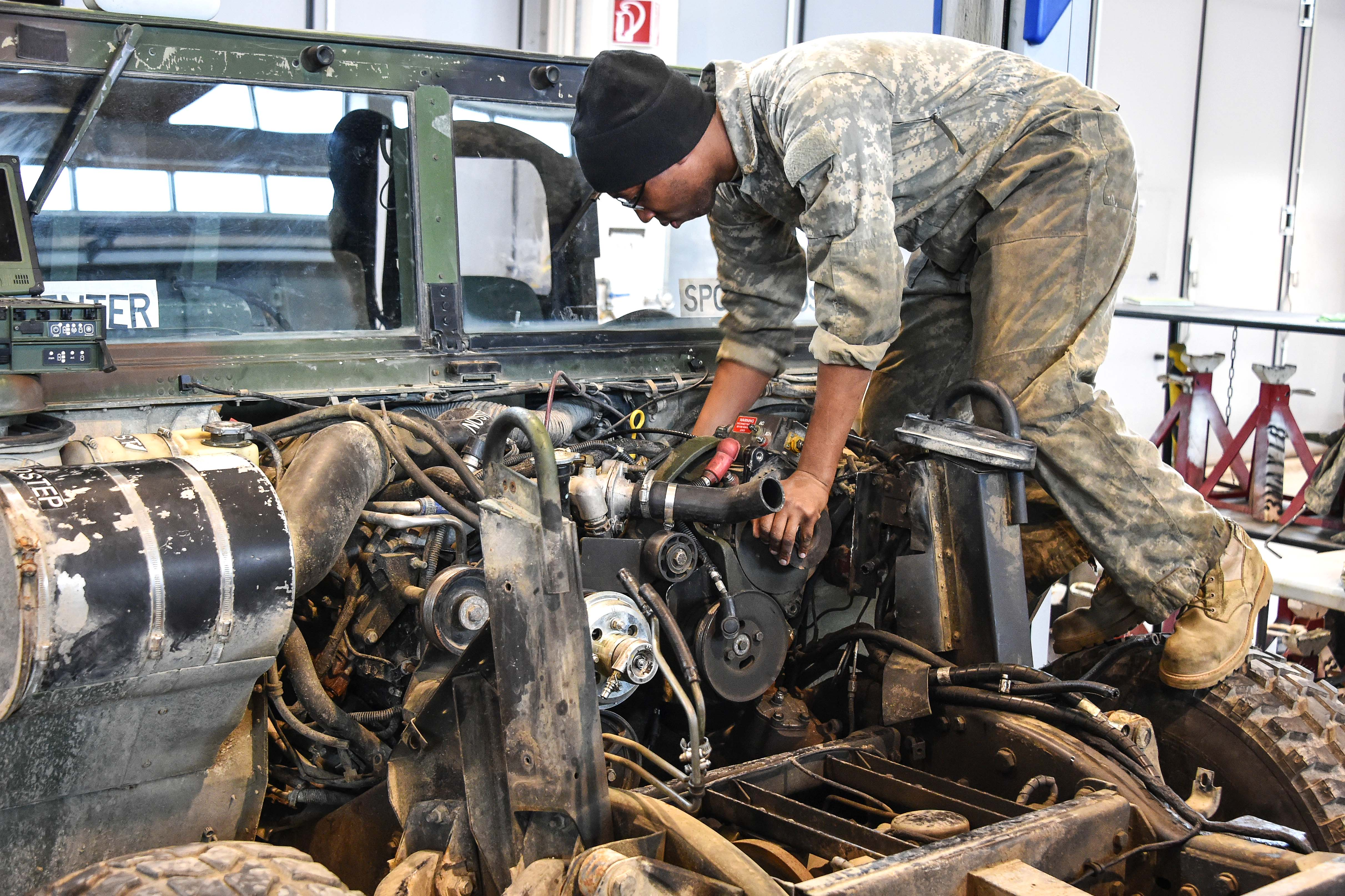 A soldier performs maintenance on a Humvee vehicle engine.