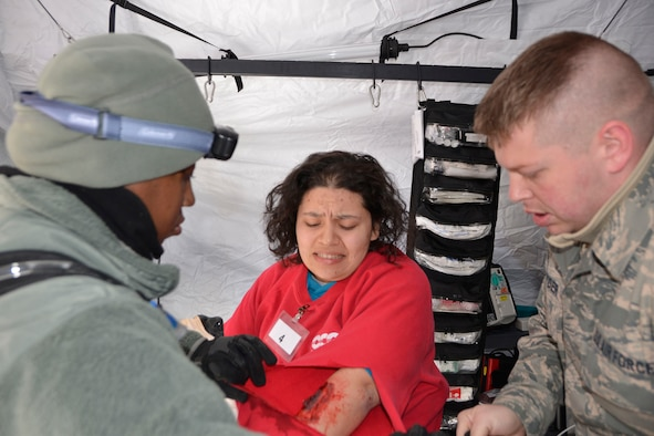 "U.S. Air Force Staff Sgt. Khaliha Love, left, and Senior Airman Glen Snyder, medics assigned to the 81st Medical Group, Keesler Air Force Base, treat a ""patient"" during the Expeditionary Medical Support (EMEDS) field confirmation exercise facility build-up portion at Camp Atterbury, Indiana, April 17, 2018. The exercise evaluates the tactics, techniques, and procedures of EMEDS during a domestic operation such as a natural disaster. (U.S. Air Force photo by Mary McHale)"