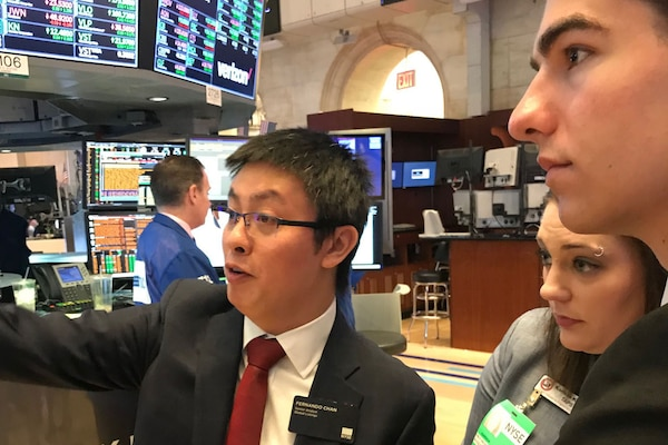 A man gives a tour for two children at the New York Stock Exchange.