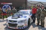 Soldiers stand around a race car at Fort Bragg, N.C.