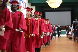 People wearing red graduation caps and gowns walk in a row.