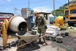 Navy seaman collects the first batch of concrete for testing.