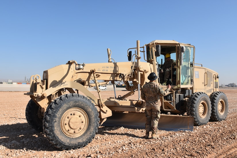Sgt. 1st Class Cody Tarr of Kittanning, Pa, discusses the project with grader operator Sgt. Jeff Labrake of Watertown, N.Y. Both Soldiers are with the 770th Engineer Company, an Army Reserve unit of engineers from Penn Yan, N.Y.