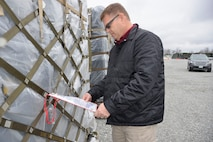 Jeff Brandenburg, chief, Air Forces Northern Medical Plans and Logistics, looks over a packing list on a pallet of medical supplies prior to the start of an Expeditionary Medical Support field confirmation exercise here April 16.