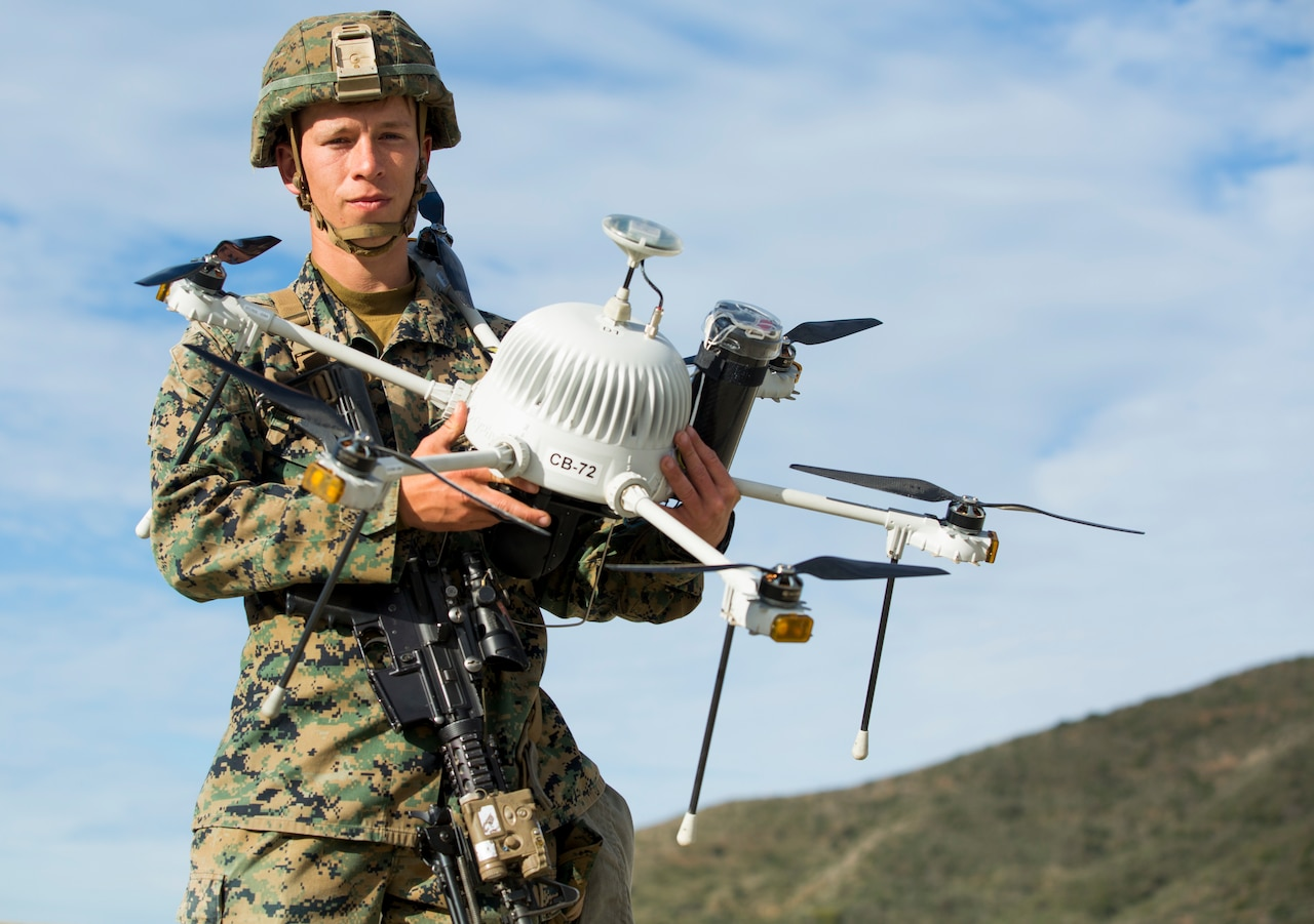 A U.S. Marine poses with a drone during Urban Advanced Naval Technology Exercise 2018 at Camp Pendleton, Calif.