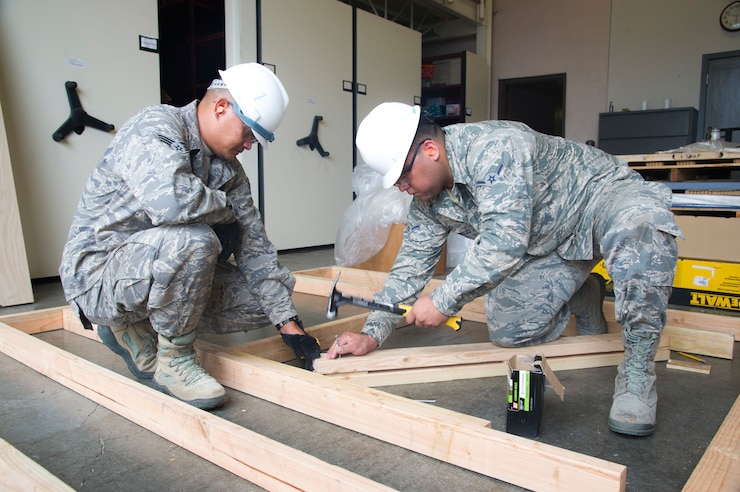 U.S. Air Force Airman 1st Class John-David Iaea ,left, and Airman Nicholas Montijo, structural engineers with the Air Force Reserve's 624th Civil Engineer Squadron build a window frame during a unit training assembly April 8, 2018, at Joint Base Pearl Harbor-Hickam, Hawaii. The 624th CES is comprised of multiple Prime Base Engineer Emergency Force and Firefighting teams ready to support worldwide deployments to construct and maintain airfield and facilities, provide firefighting support, and coordinate planning for any real world disasters. (U.S. Air Force photo by Master Sgt. Theanne Herrmann)