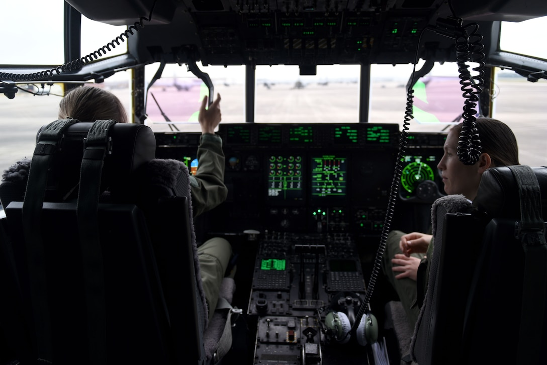 Two women are sitting in the cockpit of an aircraft.