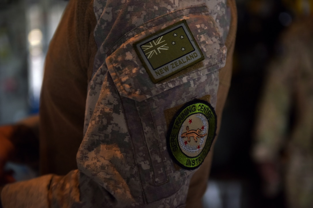 There are two patches of a military unit on an arm.