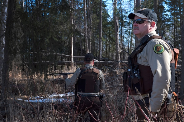 Mark Sledge, 673d Civil Engineering Squadron senior conservation law enforcement officer, and James Wendland, 673 CES chief conservation law enforcement officer, approach a black bear den at Joint Base Elmendorf-Richardson, Alaska, April 16, 2018. Making loud noises while walking the trails will alert the wildlife of your presence and reduce a surprise encounter.