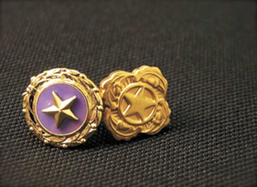 Gold star pin on grey background.