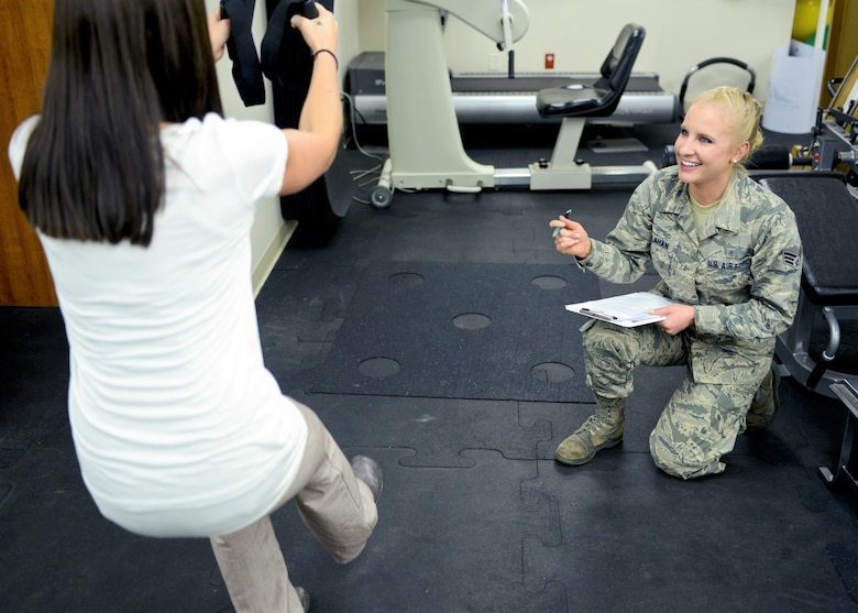 Then Senior Airman Kaitlyn Callahan, 341st Medical Operations Squadron physical medicine technician, instructs a patient through a modified squat at Malmstrom Air Force Base, Montana, July 2017. Callahan helped develop several programs to help Airmen build strength and prevent injury. (U.S. Air Force photo)