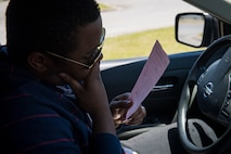 Airman 1st Class Eugene Oliver, 23d Wing photojournalist apprentice, reads a citation during a simulated distracted driving traffic stop, April 17, 2018, at Moody Air Force Base, Ga. Since January 2018 there have been 13 distracted driving incidents at Moody, which has prompted the SFS patrolmen to heavily enforce distracted driver consequences for motorists on the installation. (U.S. Air Force photo by Senior Airman Janiqua P. Robinson)