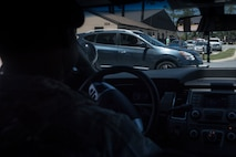 Tech. Sgt. Jamaal Smalls, 23d Security Forces Squadron (SFS) flight chief, watches Airman 1st Class Eugene Oliver, 23d Wing photojournalist apprentice, drive-by while on his cell phone during a simulated distracted driving traffic stop, April 17, 2018, at Moody Air Force Base, Ga. Since January 2018 there have been 13 distracted driving incidents at Moody, which has prompted the SFS patrolmen to heavily enforce distracted driver consequences for motorists on the installation. (U.S. Air Force photo by Senior Airman Janiqua P. Robinson)