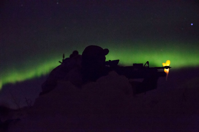 Marine with Marine Rotational Force-Europe conducts a mountainous assault on enemy position as the northern lights shine above during the field training exercise portion of Exercise White Claymore near Bardufoss, Norway, February 15, 2018. White Claymore is a U.K. Royal Marines-led training in northern Norway that focuses on winter warfare including training on movement in adverse terrain and over snow, and training in defensive and offensive operations in winter conditions.