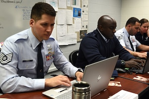 Airmen work on their computers.
