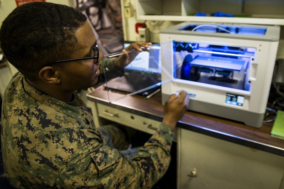 Sgt. Adrian Willis, a computer and telephone technician with Combat Logistic Battalion 31, 31st Marine Expeditionary Unit, explains the functions of a 3-D printer aboard the USS Wasp while underway in the Pacific Ocean, March 22, 2018. Marines with CLB-31 are now capable of 'additive manufacturing,' also known as 3-D printing, which is the technique of replicating digital 3-D models as tangible objects. The 31st Marine Expeditionary Unit partners with the Navy's Amphibious Squadron 11 to form the Wasp Amphibious Ready Group, a cohesive blue-green team capable of accomplishing a variety of missions across the Indo-Pacific.