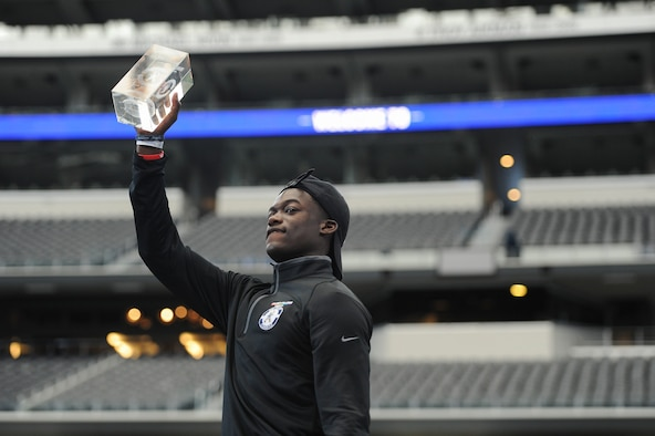 Airman Donovan V. Lewis, an Air Force technical school trainee at Goodfellow, stands with his first place trophy at the 2nd Annual Caliber Collison Military Combine finals at the Dallas Cowboys AT&T Stadium in Arlington, Texas, March 31. Lewis' first place honor earned him the distinction of announcing one of the Cowboy's fourth through seventh-round picks at the 2018 National Football League Draft April 28. (Courtesy photo by Kelby Wingert/Released)
