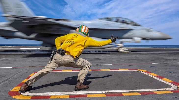 A sailor gestures while an aircraft moves in the background.