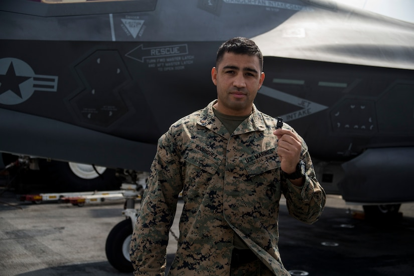 Chief Warrant Officer 2 Daniel Rodriguez, a maintenance officer with Combat Logistics Battalion 31, 31st Marine Expeditionary Unit, holds a 3-D printed plastic bumper for an F-35B Lightning II landing gear door aboard the USS Wasp while underway in the Pacific Ocean, April 19, 2018. Marines with CLB-31 are now capable of 'additive manufacturing,' also known as 3-D printing, which is the technique of replicating digital 3-D models as tangible objects.  The 31st Marine Expeditionary Unit partners with the Navy's Amphibious Squadron 11 to form the Wasp Amphibious Ready Group, a cohesive blue-green team capable of accomplishing a variety of missions across the Indo-Pacific.