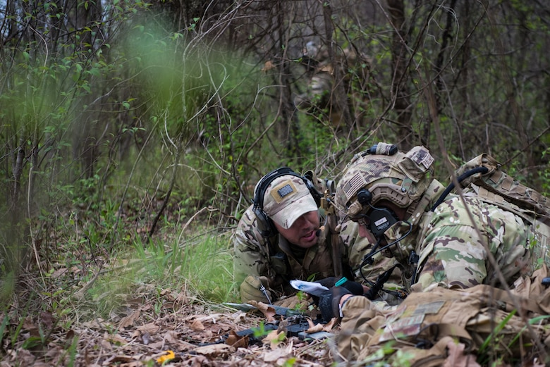 A Tactical Air Control Party specialist talks with an instuctor while participating in a field training exercise, or FTX, at Fort Chaffee Maneuver Training Center in Arkansas, April 14, 2018. The FTX, April 13-17, 2018, took place at the end of a two-month Initial Combat Skills Training Course, which is hosted by the 138th Combat Training Flight at Will Rogers Air National Guard Base in Oklahoma City, and is the only one of its kind in the U.S. Air Force. (U.S. Air National Guard Photo by Staff Sgt. Kasey M. Phipps)