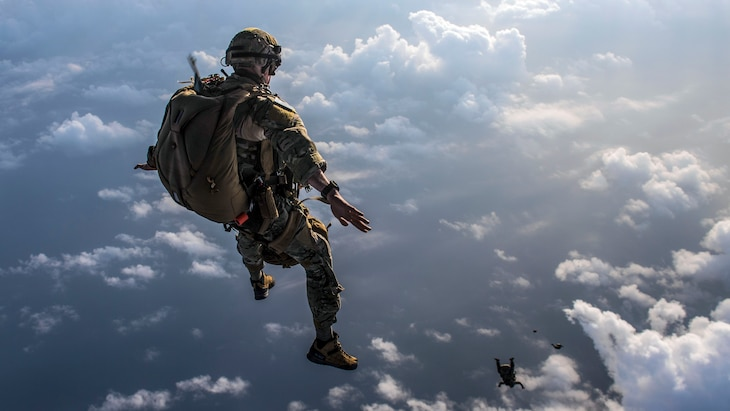 Airmen jump out of an aircraft.