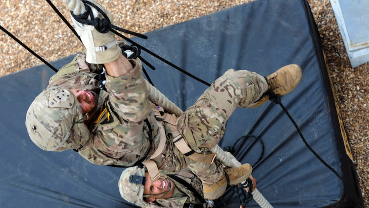 A soldier climbs a rope as another soldier watches from below.