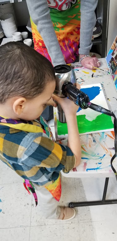 An Exceptional Family Member Program participant dries his artwork after a Creative Art Afternoon Jan. 19, 2018, at a local paint gallery. The EFM Program offers EFMP families the opportunity to partake in various activities/camps throughout the year. (Courtesy photo)