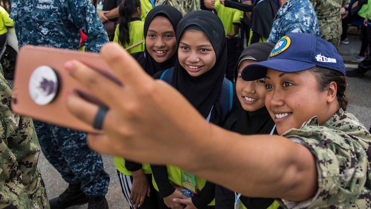 A sailor holds a phone to take a group photo.