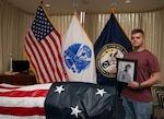 U.S. Army Spc. Zachary Boney poses next to the remains of his deceased great grandfather, U.S. Army Master Sgt. Finley Davis during a tour of the Defense POW/MIA Accounting Agency (DPAA) on Joint Base Pearl Harbor - Hickam, Hawaii, April 16, 2018. Master Sgt. Finley served in Delta comany, 2nd engineer battalion, 2nd Infantry Division when he was captured as a prisoner of war in Kunu-ri, camp 5, North Korea. (U.S. Army Photo by Staff Sgt. Jamarius Fortson)