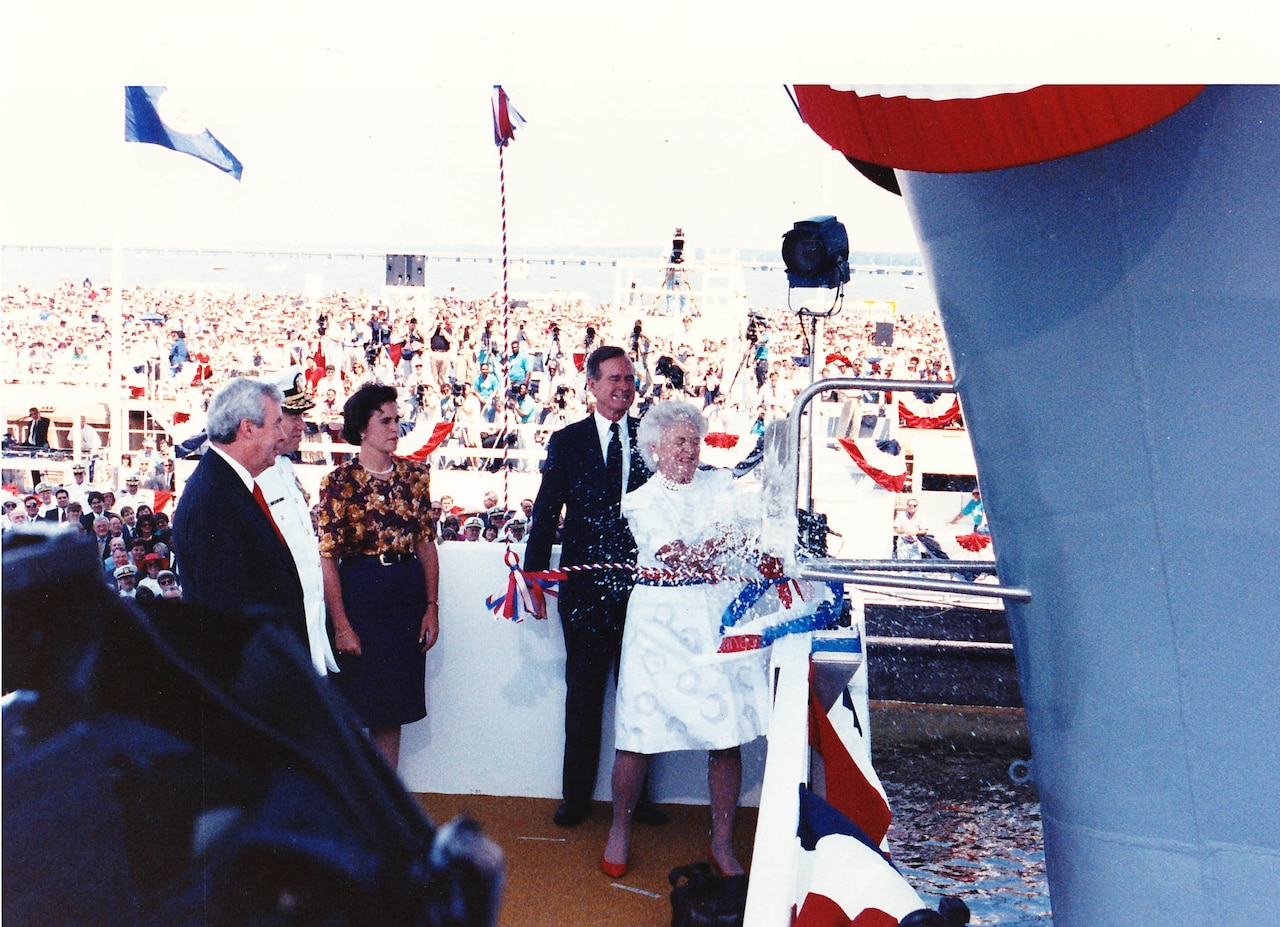 Ship sponsor first lady Barbara Bush breaks a bottle of champagne on the bow of the aircraft carrier USS George Washington as President George H.W. Bush looks on in Newport News, Va., July 21, 1990.