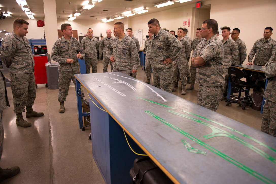 Staff Sgt. Ryan Bessery, 56th Component Maintenance Squadron Egress technician, second from left, briefs Brig. Gen. Brook Leonard, 56th Fighter Wing commander, fifth from left, on new measurement templates for F-35 Lightning II canopy maintenance produced in house April 13, 2018, at Luke Air Force Base, Ariz. Along with other innovations, the egress section has used in-house production of the templates to significantly reduce the replacement time on flexible linear shaped charges in F-35 canopies. (U.S. Air Force photo by Senior Airman Ridge Shan)