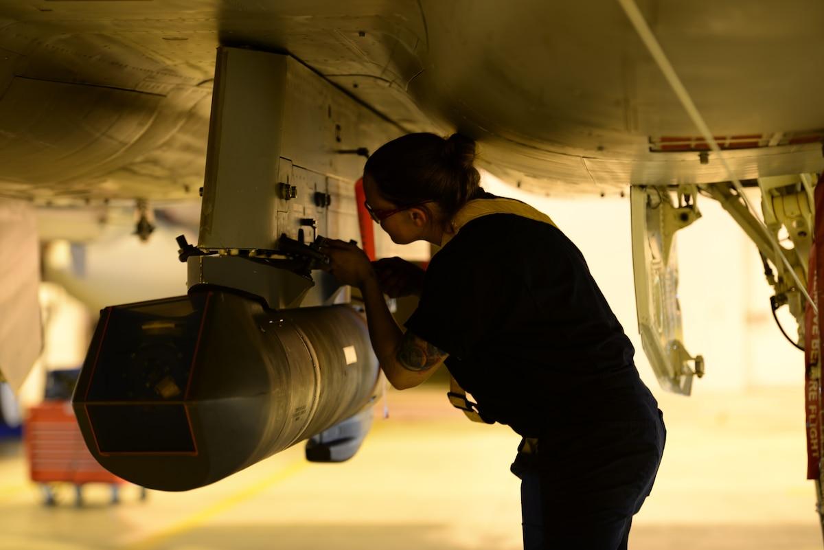An airman examines part of an aircraft.