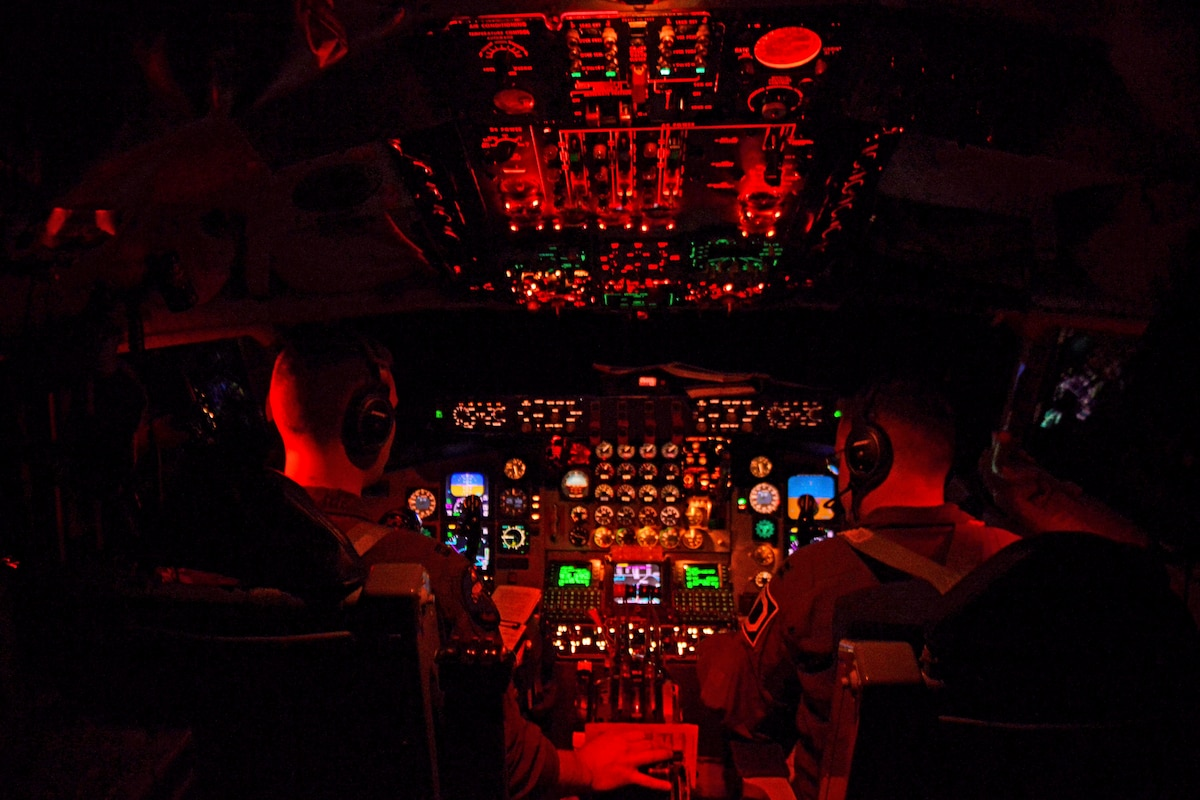 Red light casts a glow on the interior of a cockpit with two pilots at the controls.