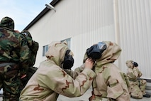 U.S. Airmen assigned to the 86th Civil Engineer Group on Ramstein Air Base, Germany, assist each other in donning protective gear during an exercise training service members to respond to chemical, biological, radiological, and nuclear threats, April 12, 2018. The Air Force requires service members to maintain ample knowledge of CBRN operations regardless of rank or career field. (U.S. Air Force photo by Senior Airman Joshua Magbanua)