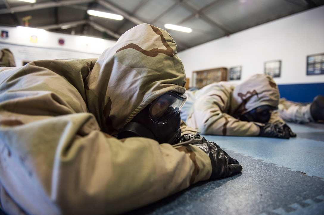 U.S. Airmen assigned to the 86th Civil Engineer Group take cover during a chemical, biological, radiological, and nuclear training exercise on Ramstein Air Base, Germany, April 12, 2018. CBRN training involves familiarization of the use of protective gear, which includes practicing putting on masks, rubber boots, gloves, and protective suits in a hazardous environment. (U.S. Air Force photo by Senior Airman Joshua Magbanua)