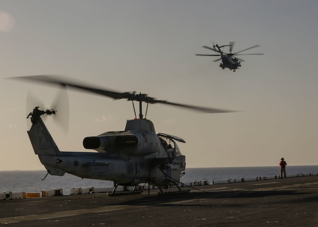 A CH-53E Super Stallion flies over an idling AH-1W Super Cobra, both with 2nd Marine Aircraft Wing, on the deck of the USS Kearsarge, April 18, 2018. The aircraft arrive in support of Navy Week New Orleans, providing the opportunity for the public to learn about interoperability between the Marine Corps and Navy.
