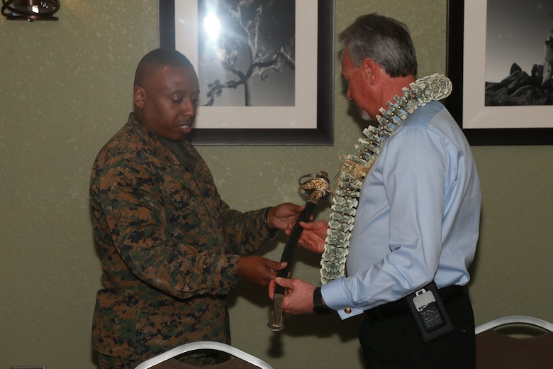 Brig. Gen. Dimitri Henry, U.S. Marine Corps Director of Intelligence, presents Larry Stratton, former Deputy Director of Marine Corps Community Services, a non-commissioned officer's sword as a gift during Stratton's retirement ceremony at the Frontline Restaurant aboard the Marine Corps Air Ground Combat Center, Twentynine Palms, Calif., March 29, 2018. Stratton, a retired Marine Corps master sergeant, was Henry's drill instructor at Marine Corps Recruit Depot San Diego, Calif., in 1981.