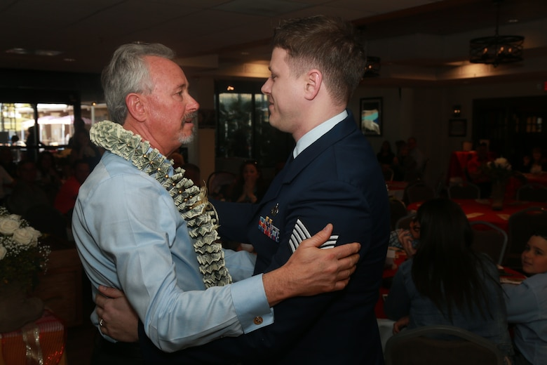 Larry Stratton, former Deputy Director of Marine Corps Community Services, embraces his son, U.S. Air Force Tech Sgt. Jared Stratton during Larry's retirement ceremony at the Frontline Restaurant aboard the Marine Corps Air Ground Combat Center, Twentynine Palms, Calif., March 29, 2018. Stratton, a retired Marine Corps master sergeant, retired from civil service after a combined 44 years of military and government service.