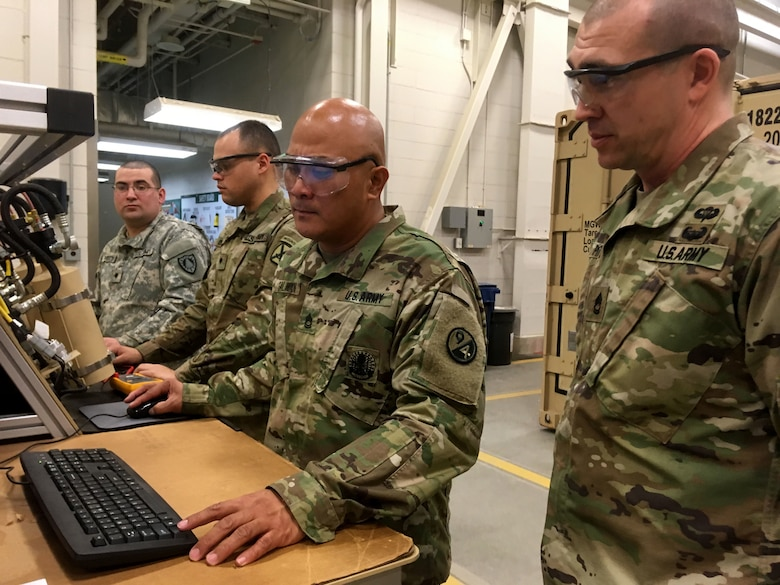 Sgt. 1st Class Gilbert Galman, a 94th Training Division instructor at Regional Training Site - Maintenance (RTS-M) Devens, reviews the digital results of a student's diagnostic preventative maintenance checks and services test during the 91B Wheeled Vehicle Mechanic Course, 28 March 2018. Galman currently holds the mantle of Instructor of the Year at RTS-M Devens after the leadership chose him in October 2017 following a rigorous board selection process. He went on to represent Devens the next month at the 2017 Instructor of the Year competition sponsored by the 80th Training Command (TASS). According to his supervisors, Galman pushes his students to excel and his passion and dedication enhances the entire team at RTS-M Devens. (U.S. Army Reserve photo by Master Sgt. Benari Poulten, 80th Training Command)