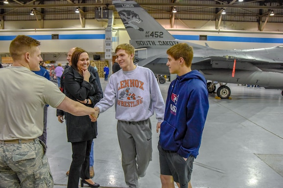 Airmen first class Slade Mutchelknaus, 114th Maintenance Squadron munitions handler, talks with Jaetin DeCou and Tyson Stoebner, juniors from Lennox High School, about his career field during Night Flying Career Day at Joe Foss Field, S.D. on April 17, 2018.